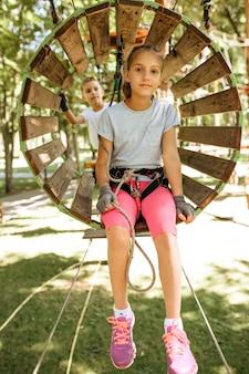 機器で笑顔の子供たちはロープパーク、遊び場に登ります。吊橋に登る子供たち