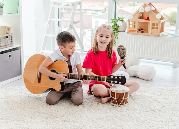 현대 아파트에서 드럼과 기타 연주 웃는 아이