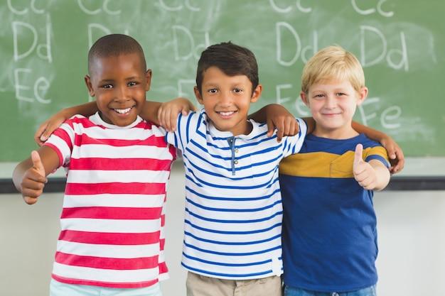 教室で親指を現して子供たちの笑顔