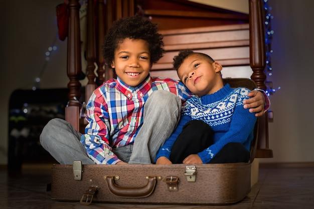 笑顔の子供たちはスーツケースの中に座っています。階段の近くのうれしそうなアフロの男の子。兄弟がいて幸せです。あなたが愛する人の世話をしてください。