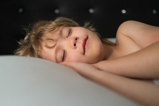 ベッドで寝ている子供たちの笑顔。良い夢を。白い枕。小さな天使の夢。