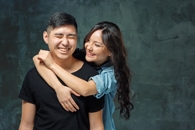 Smiling korean couple on gray