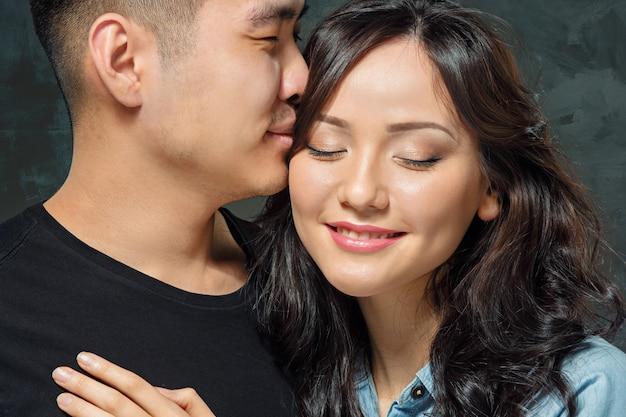 Smiling korean couple on gray
