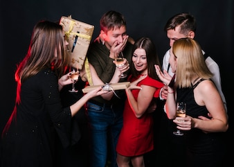 Smiling ladies and amazed guys with glasses of drinks and present boxes