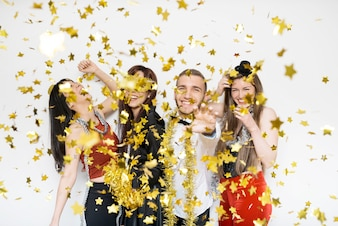 Smiling ladies and guy in evening wear between ornament confetti