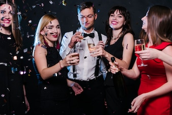Smiling ladies and guy in evening wear with glasses of drinks between tossing confetti