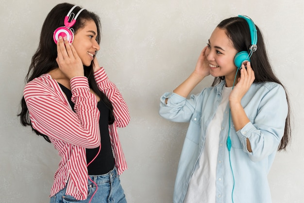Smiling ladies standing in color headphones and looking at each other