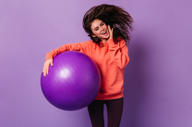 Smiling lady in bright sweatshirt and dark leggings jumps on purple wall, holding fitball
