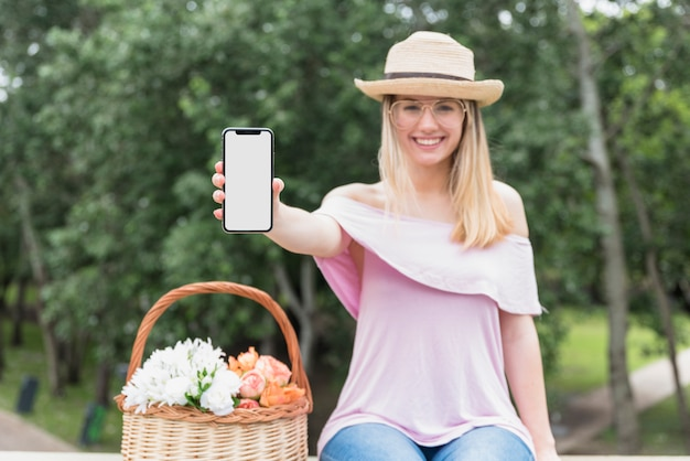 Smiling lady in eyeglasses and hat showing mobile phone