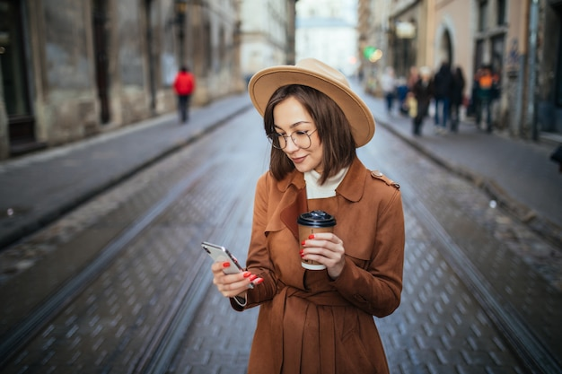 Smiling lady has a videocall and drinks coffee while walking outdoors in the city