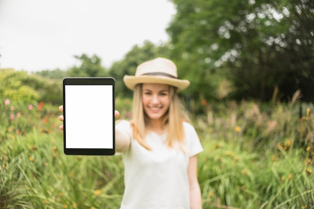 Smiling lady in hat showing tablet near grass