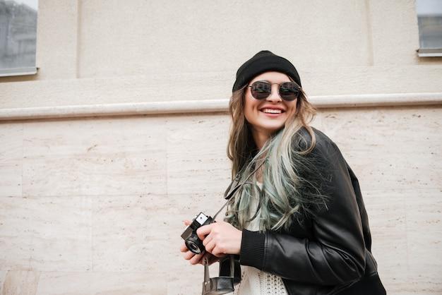Smiling lady holding camera.