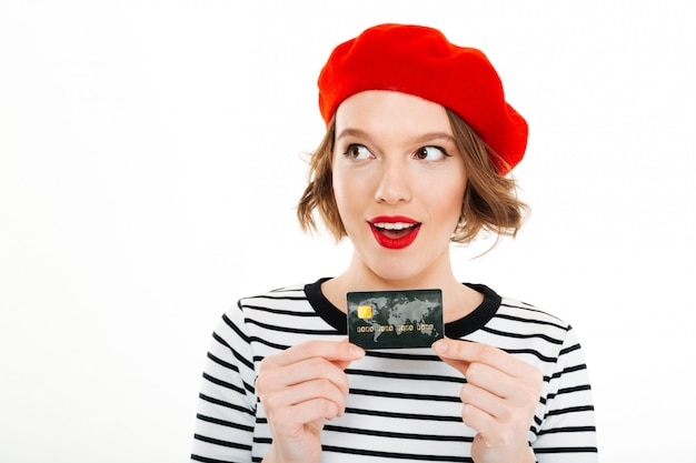 Smiling lady holding credit card and looking aside isolated
