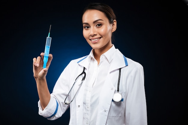 Smiling lady holding syringe and looking