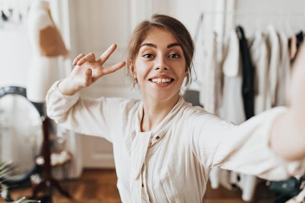 ブラウスの笑顔の女性は自分撮りを取り、ピースサインを示しています