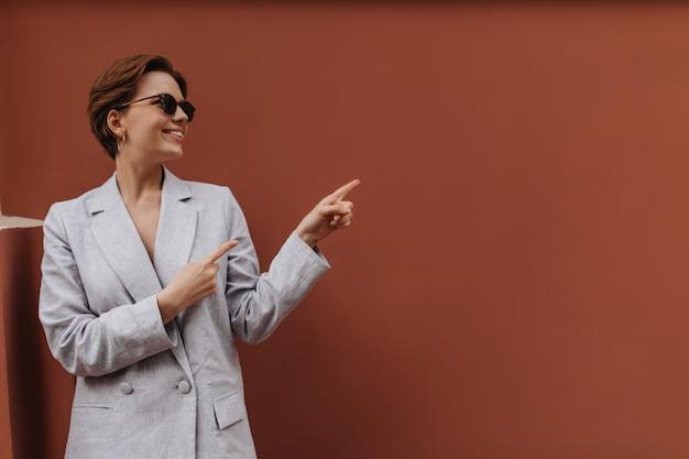 灰色の服を着た笑顔の女性は、テキストを配置することを指しています。サングラスと特大のジャケットで幸せな若い女性は心から外で微笑む