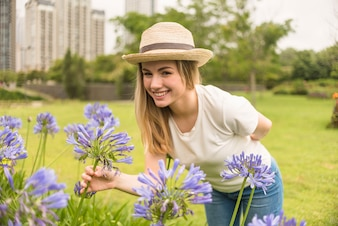 Smiling lady in hat holding blue blooms in city park