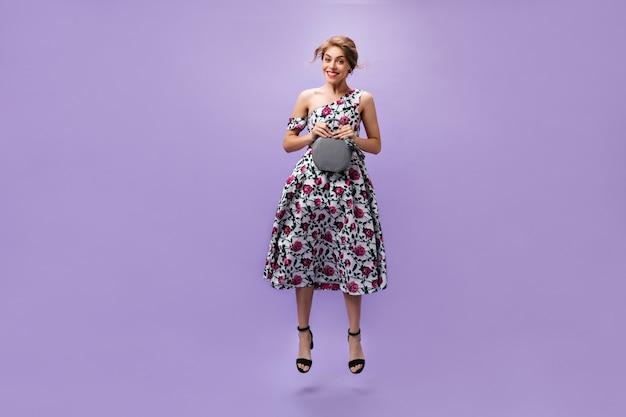 ミディドレスの笑顔の女性は、ハンドバッグを保持し、紫色の背景にジャンプします。灰色のバッグでポーズをとってクールな服を着た美しい若い女性。