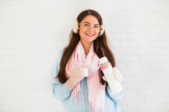 Smiling lady in mittens, earmuffs and scarf with thermos