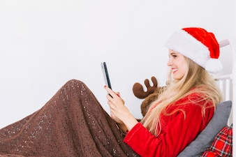 Smiling lady in party hat lying on bed with tablet