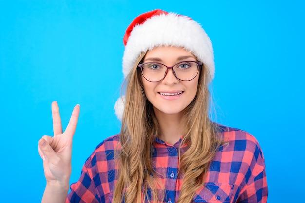 산타 모자 승리 기호를 보여주는 웃는 여자