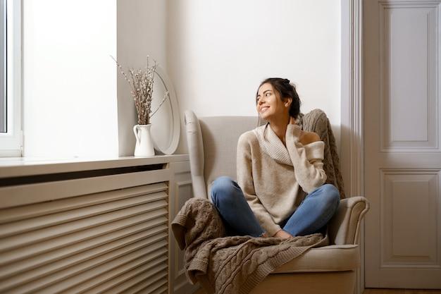 スマートな流行の服を着た笑顔の女性が肘掛け椅子に座っています。笑顔、室内でリラックスした雰囲気の中で座って