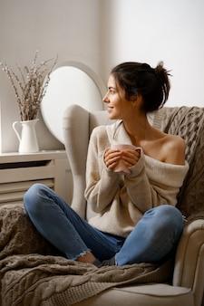 스마트 유행 착용에 웃는 아가씨는 차 한잔과 함께 안락의 자에 앉아있다.