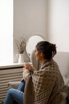 スマートな流行の服を着た笑顔の女性は、お茶を片手に肘掛け椅子に座っています。
