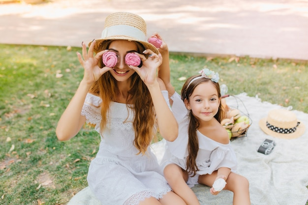 眼鏡のようなピンクのジンジャーブレッドを保持し、娘と一緒に毛布の上に座っている白いドレスの笑顔の女性。ピクニック中に冗談を言っている母親の隣でポーズをとるリボンを持つかわいい女の子。