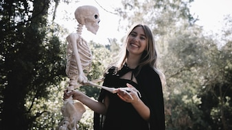 Smiling lady in witch clothes holding skeleton