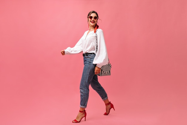 Smiling lady in jeans, white blouse walking on pink background.  fashionable woman in red sunglasses steps on isolated backdrop.