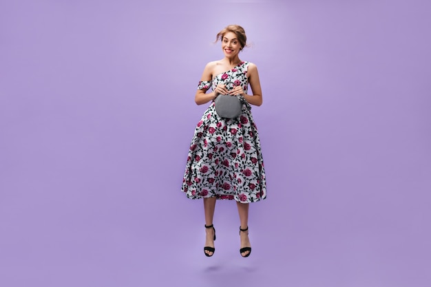 Smiling lady in midi dress holds handbag and jumps on purple background. beautiful young woman in cool clothes posing with gray bag.