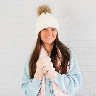 Smiling lady in mittens, bobble hat and scarf