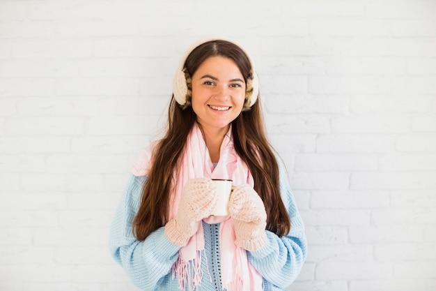 Signora sorridente in guanti, paraorecchie e sciarpa con coppa