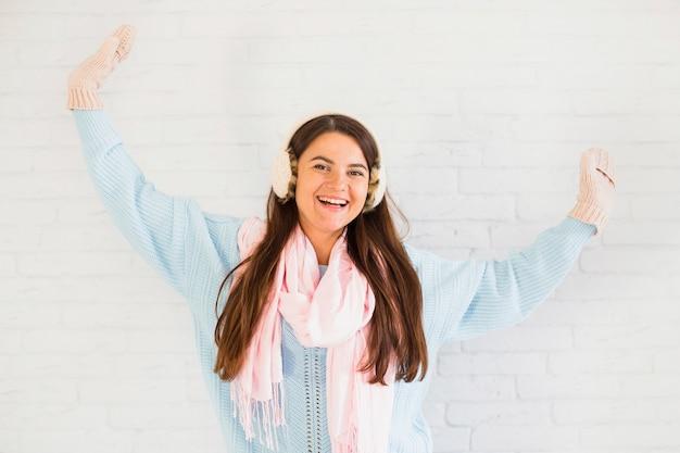 Signora sorridente in guanti, paraorecchie e sciarpa con le mani alzate
