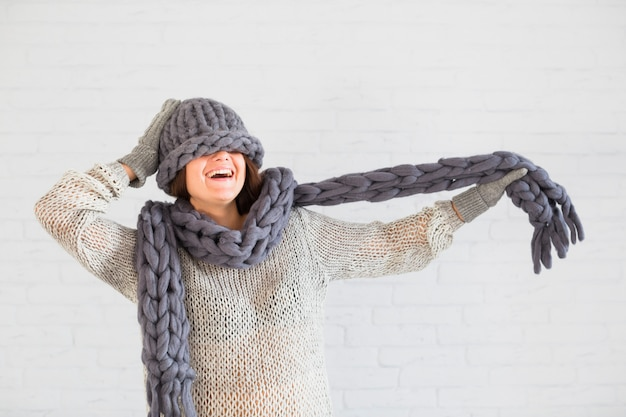 Smiling lady in mittens and hat on eyes with scarf in hand