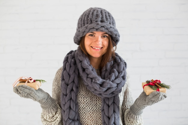 Smiling lady in mittens, hat and scarf with gift boxes