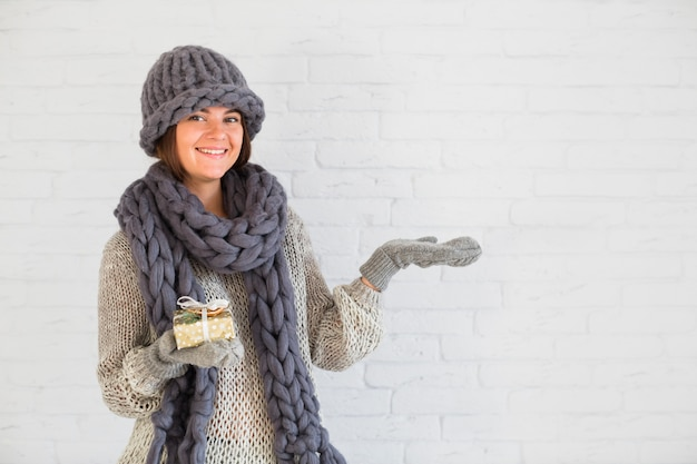 Smiling lady in mittens, hat and scarf with present box and opened hand