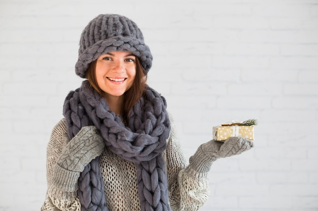 Smiling lady in mittens, hat and scarf with present box