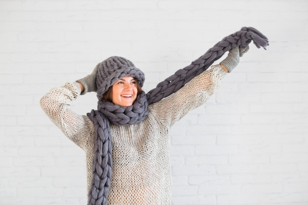 Smiling lady in mittens and hat with scarf in upping hand