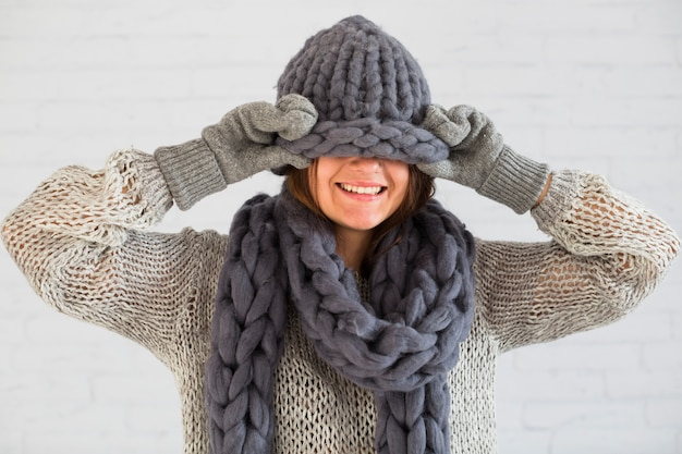 Smiling lady in mittens, scarf and hat on eyes