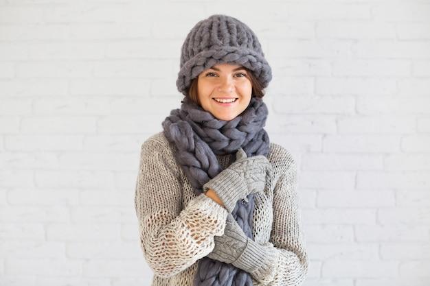 Signora sorridente in guanti, cappello e sciarpa