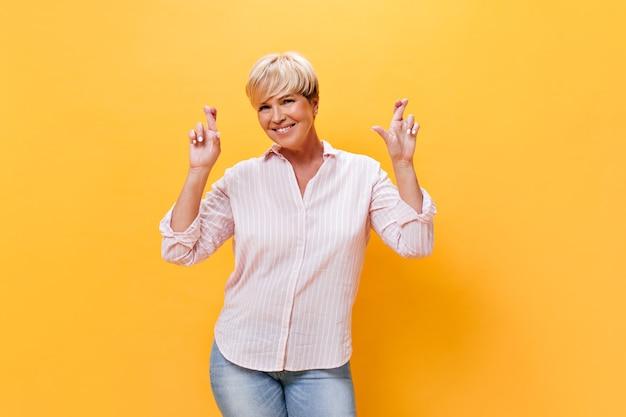 분홍색 셔츠에 웃는 여자는 주황색 배경에 손가락을 교차