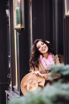 La signora sorridente posa prima delle finestre di legno scure