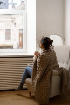 La signora sorridente in abbigliamento alla moda intelligente è seduta sulla poltrona con una tazza di tè.