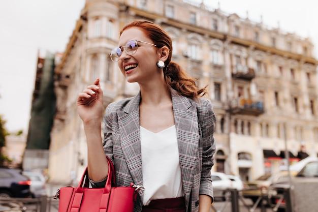 La signora sorridente in occhiali alla moda tiene la borsa rossa