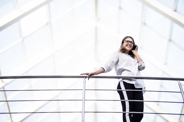白いtシャツを着た女性の成功したビジネスの女性が休んで立っていると近代的なオフィスセンターのバルコニーを見渡す笑顔の女性