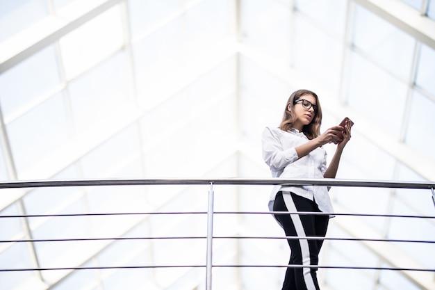 Sorridente donna d'affari di successo donne in piedi a riposo e guardando attraverso sul balcone nel moderno centro ufficio vestito in t-shirt bianca