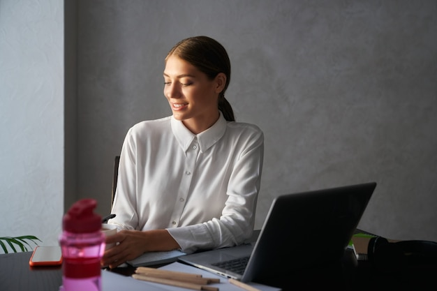 Smiling lady using laptop while working at home