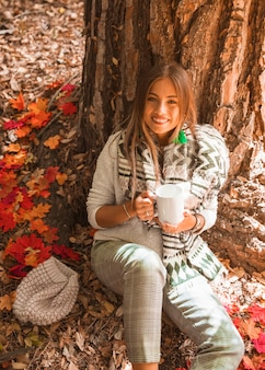 Smiling lady with beverage in autumn forest